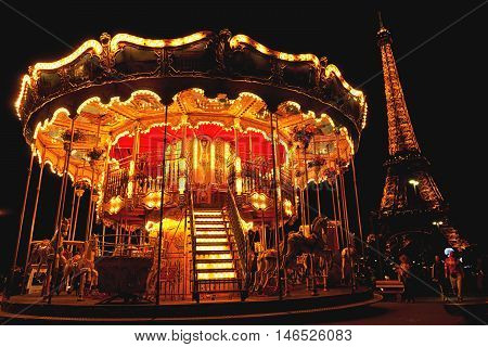 Paris France - September 06 2011 - Spinnig carousel with Eiffel tower in the background during the light show