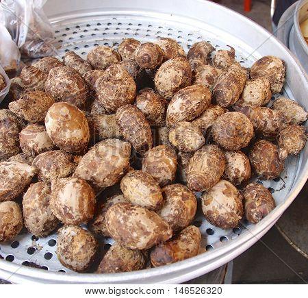 Fresh taro for sale closeup in market .