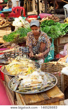 Yangon Myanmar - February 24 2011 - Young Burmese woman selling fresh seafood in the street market.
