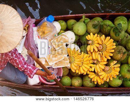 Damnoen Saduak Thailand - March 21 2011 - Senior Thai woman with a hat on a boat full of fruits in Damnoen Saduak Floating Market