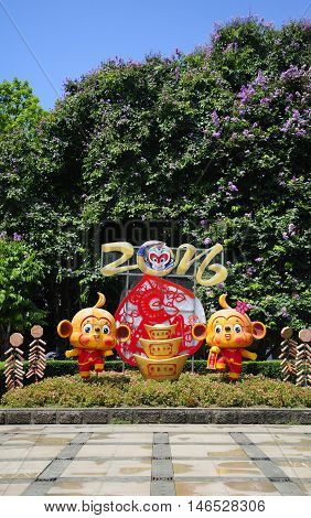 A 2016 year of the monkey display near a pot containing the chinese words meaning gold or wealth at a park in Guangzhou China in Guangdong province.