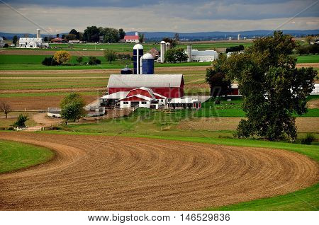 Lancaster County Pennsylvania - October 14 2015: Freshly plowed fields and an Amish farm with barns and silos
