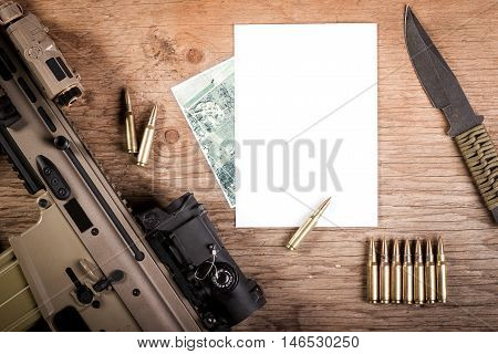 Assault rifle and blank paper on a wooden table