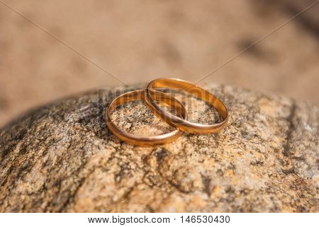 Two gold wedding rings lying on a rock