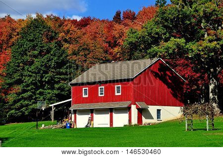Lancaster County Pennsylvania - October 15 2015: Red wooden barn wth three white doors surrounded by colourful Autumn foliage