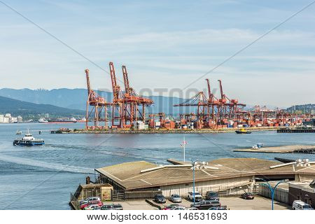 Vancouver, Canada - April 19, 2016: Industrial port with cranes, ships, cars and helicopter landing at the harbour