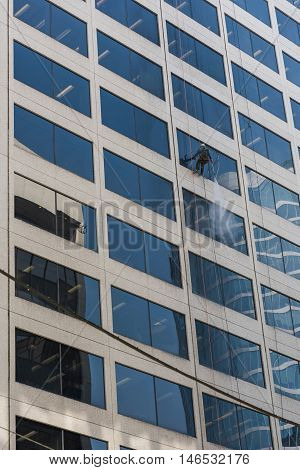 Vancouver, Canada - April 19, 2016: Cleaning worker hanging on scaffold spraying windows on skyscraper with water
