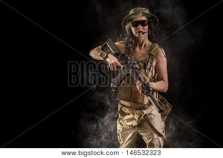 sexy girl with assault rifle on black background
