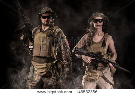 man and woman with assault rifles on a black background
