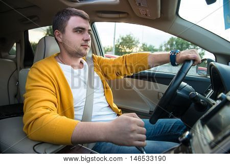 Man driving luxury car. Concept photo of safety driving with seatbelt.