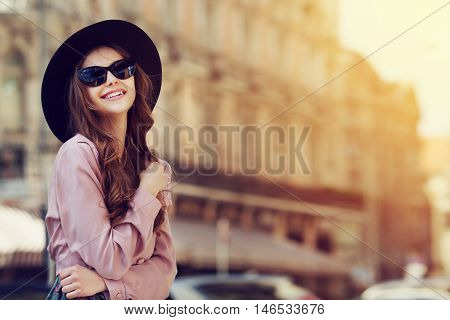 Outdoor portrait of a young beautiful fashionable happy lady posing on a street of the old city. Model wearing stylish clothes. Girl looking up. Female fashion. City lifestyle. Copy space for text.