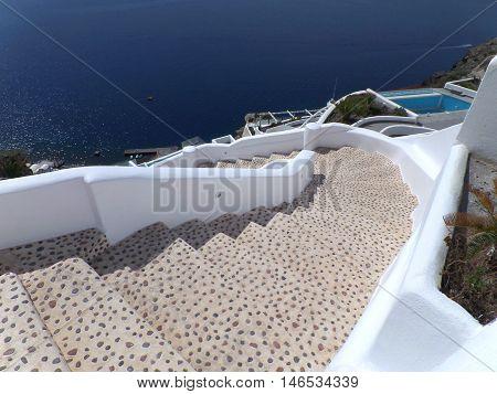 White Staircase to the Beach and Deep Blue Sea, Oia Village on Santorini Island, Greece