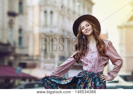 Outdoor portrait of a young beautiful fashionable happy lady posing on a street. Model wearing stylish clothes. Girl looking at camera. Female fashion. City lifestyle. Copy space. Toned.