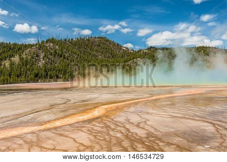 Rising blue steam and mist from Grand Prismatic hot spring in Midway Geyser basin at Yellowstone National Park with red bacterial patterns
