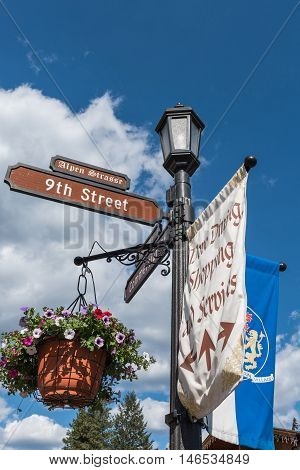 Street sign in bavarian village of Leavenworth, Washington with flower pots and Alpen Strasse