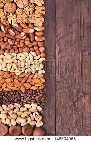 Variety nuts background from left side of old wooden background