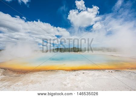 Rainbow pool in Black Sand Basin in Yellowstone National Park with orange and light blue colors with steam rising