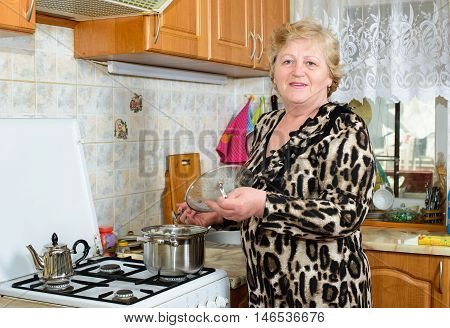 Happy Senior woman cooking at the kitchen