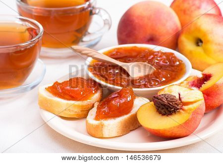 Sweet peach jam on bread and bowl horizontal