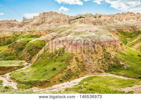 Dried up stream in Badlands National Park with green grass and canyons