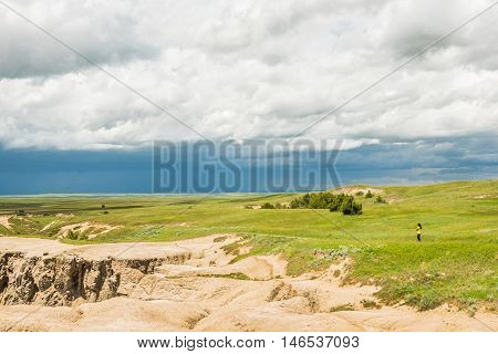 Badlands National Park, USA - May 25, 2016: Dark blue rain storm clouds contrast with green prairie steppe grass valley with person standing