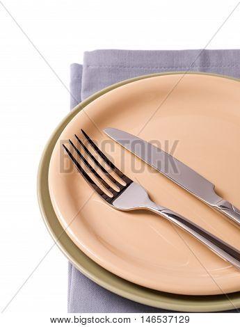 Plates with silverware on gray napkin on white