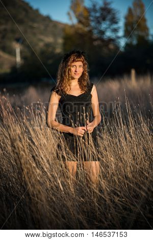 Young female standing in autumn tall dry hay grass and holding it in black dress and ginger hair smiling
