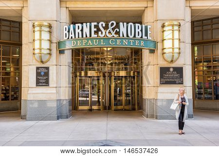 Chicago, USA - May 30, 2016: Entrance to Barnes and Noble bookstore in downtown city at DePaul University center with gold detailed decoration and revolving doors, people walking