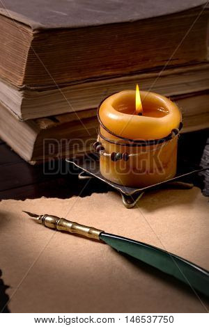 Quill pen on old paper, candle and  books