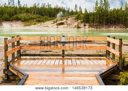 Green Sour lake in Yellowstone National Park with boardwalk sign and hot spring at Mud Volcano area
