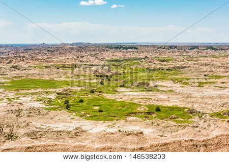 Landscape view of Badlands National Park sandstone canyons in desert with green grass and plants