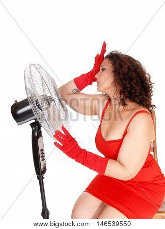 A young woman sitting very hot in the heat in front so a big fan to get some cool air isolated for white background.