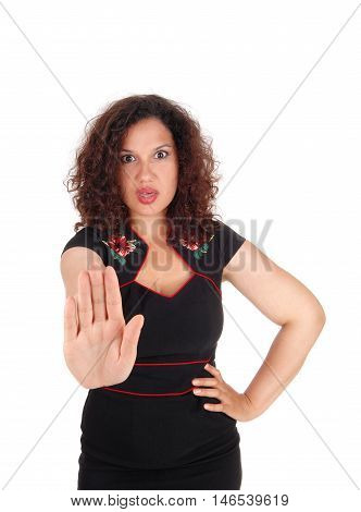 A angry young woman in a black dress holding her hand up and telling come not close isolated for white background.