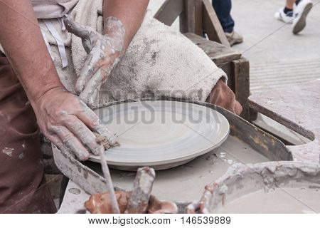 A male potter at work with his pottery wheel