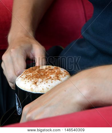 Cup of foamy cappuccino on a man¨'s hand