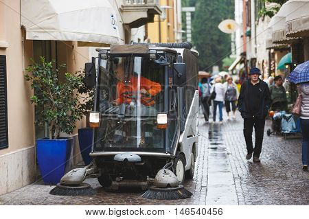 Sirmione Italy - May 09 2016: The machine cleans the pedestrian street in rainy weather
