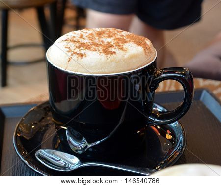Cup of delicious foamy cappuccino on a plate