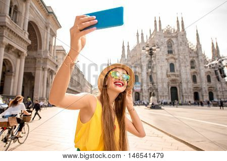 Young female tourist making selfie photo with smart phone in front of the famous Duomo cathedral in Milan. Happy vacations in Milan