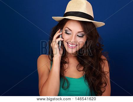 Happy beautiful makeup woman talking on mobile phone in summer hat and looking down on bright blue background