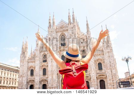 Back view on young tourist with backpack and hat looking on the famous Duomo cathedral in Milan. Having great vacations in Milan