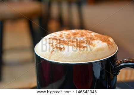 Cup of foamy cappuccino on a wooden table. Closeup.