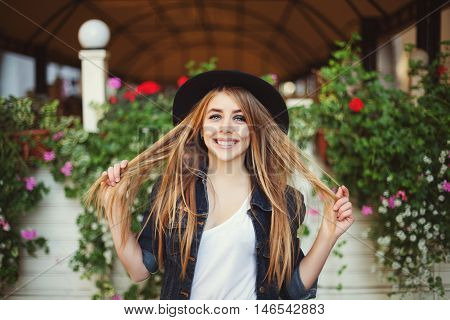 Portrait of cute naughty girl playing with her hair. Colorful background.