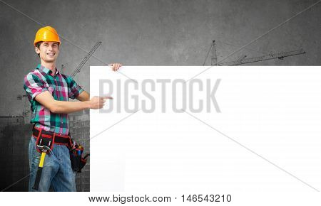 Young builder man pointing with finger at white blank banner. Place your text
