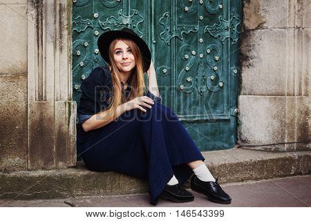 Street full body portait of stilylish smiling young woman sitting near the door. Model looking at camera. City lifestile.