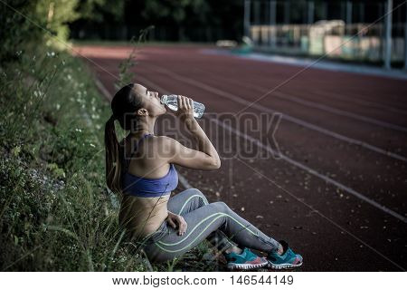 Young Sporty Woman Drinking Water After Running In The Stadium, Close-up