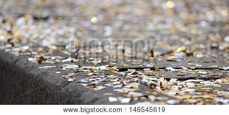 festival background with gold and silver sequins that lie on the pavement and the road and bokeh