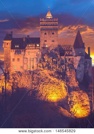 Beautiful view of Dracula castle (medieval architecture) in Bran town, illuminated at night, in Transylvania region, Romania, Eastern Europe