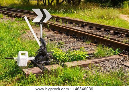 Railroad switch with a new painting on a bright Sunny day among the green grass