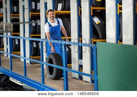 Smiling mechanic pushes the tire in tire store