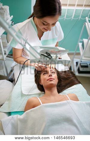 Cheerful cosmetologist treats the face of a woman with microdermabrasion treatment looking through a magnifying glass